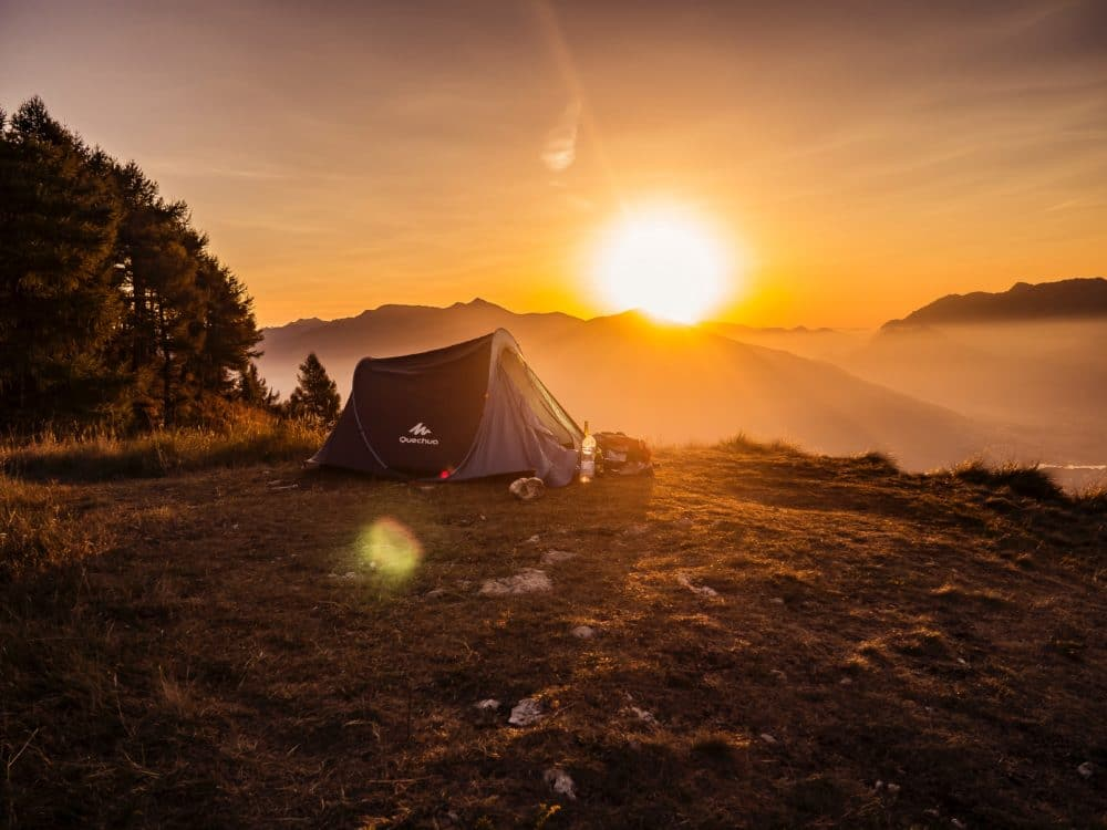 Dome tent on a mountain under the bright yellow sun.