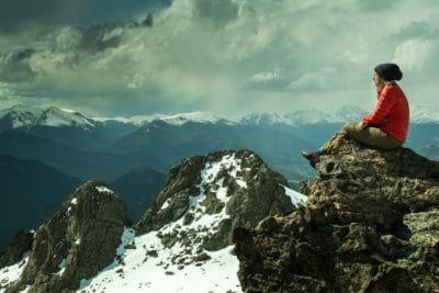 A girl sitting on a rock ledge in the snowy mountains.