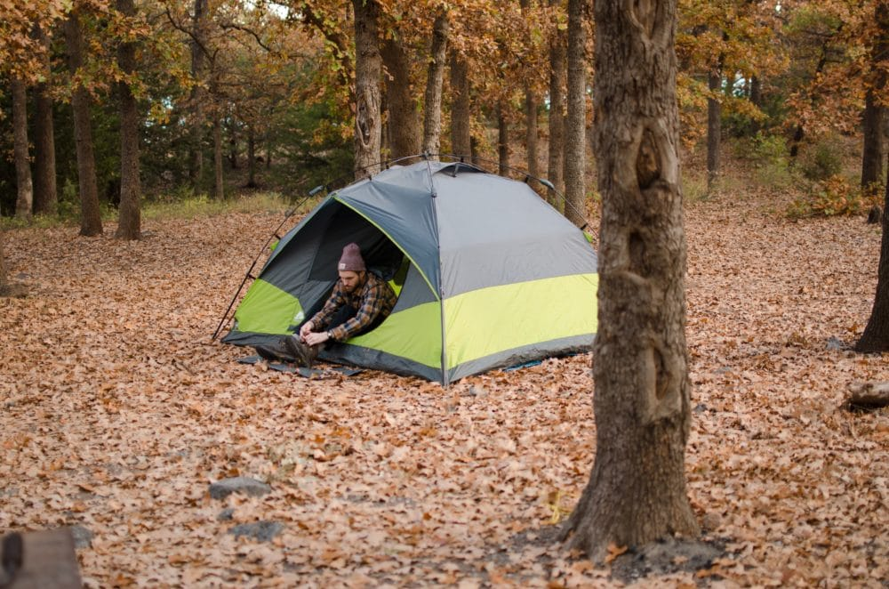 Person sitting in a tent with orange leaves around him.