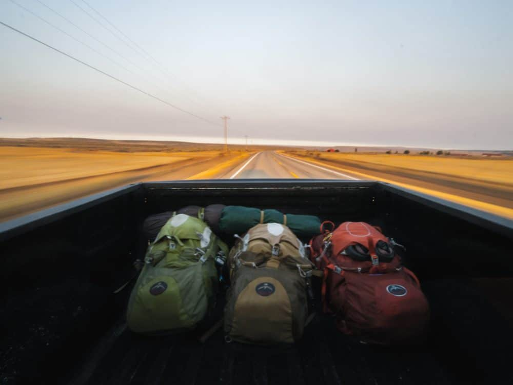 Three backpacking backpacks in the bed of a truck.