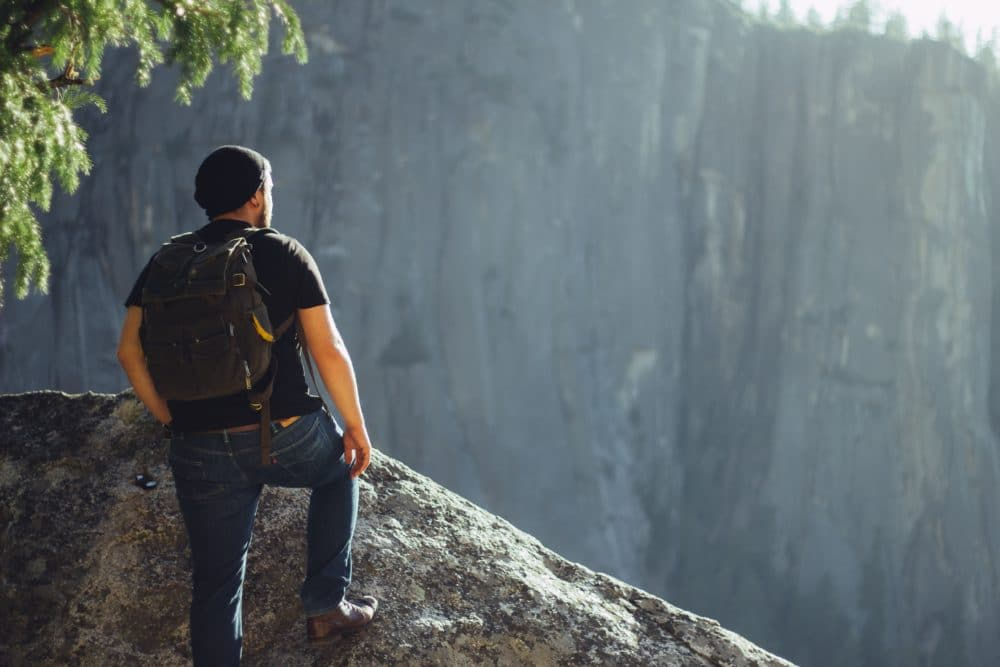 Man in jeans standing on a rock outside.