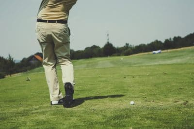 A man golfing on a green golf course.