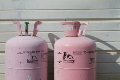Two pink propane tanks and a white wall.