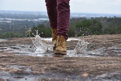 A person with brown hiking boots stepping in a puddle of water outside.