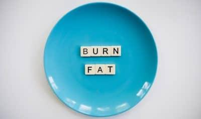 Burn fat text blocks on a round blue ceramic plate.