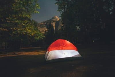 Red and white camping tent surrounded by trees during the nighttime.