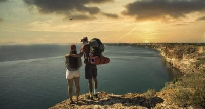 A couple standing on a mountain cliff by a body of water.