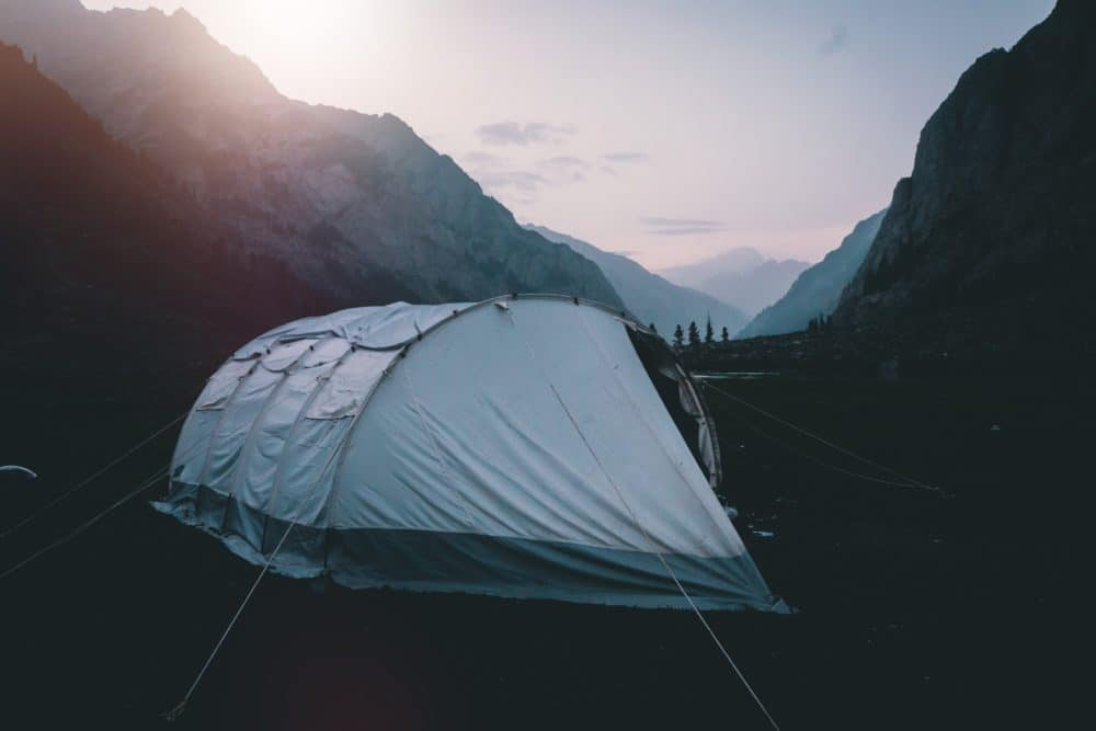 A large white tent in the mountains.