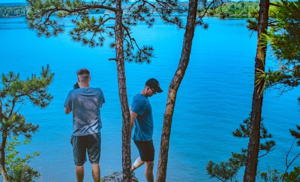 Two men by a blue lake in Arkansas.