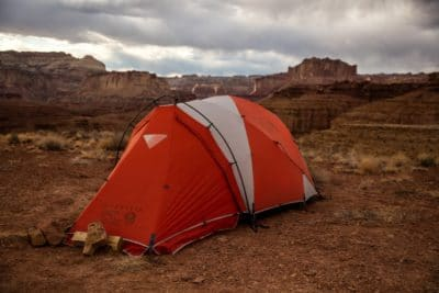 Red and white dome tent on dry dirt.