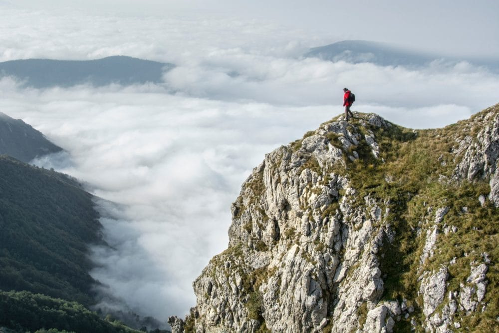photography-of-person-on-green-mountain-691034