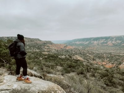 Woman standing on a rock overlooking a canyon in Texas.