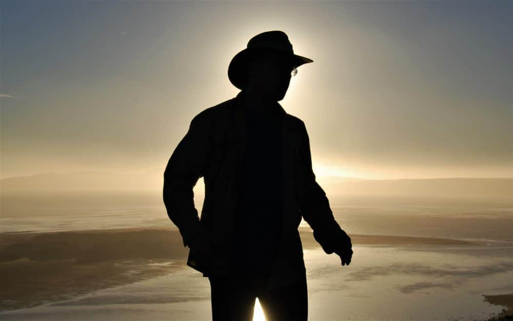 A silhouette of a man with a hat on.