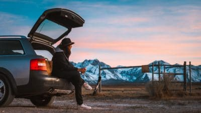 Man sitting in a car's tail looking at the mountains during sunset.