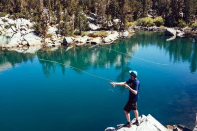 A man fishing by a blue body of water.