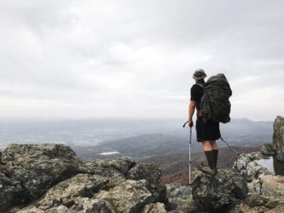 A man with hiking poles on a mountain.