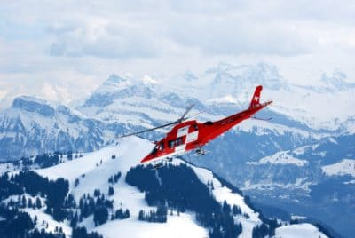 A red helicopter in the sky surrounded by snowy mountains.