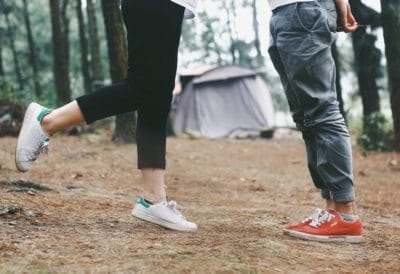 Two people standing in a campsite.
