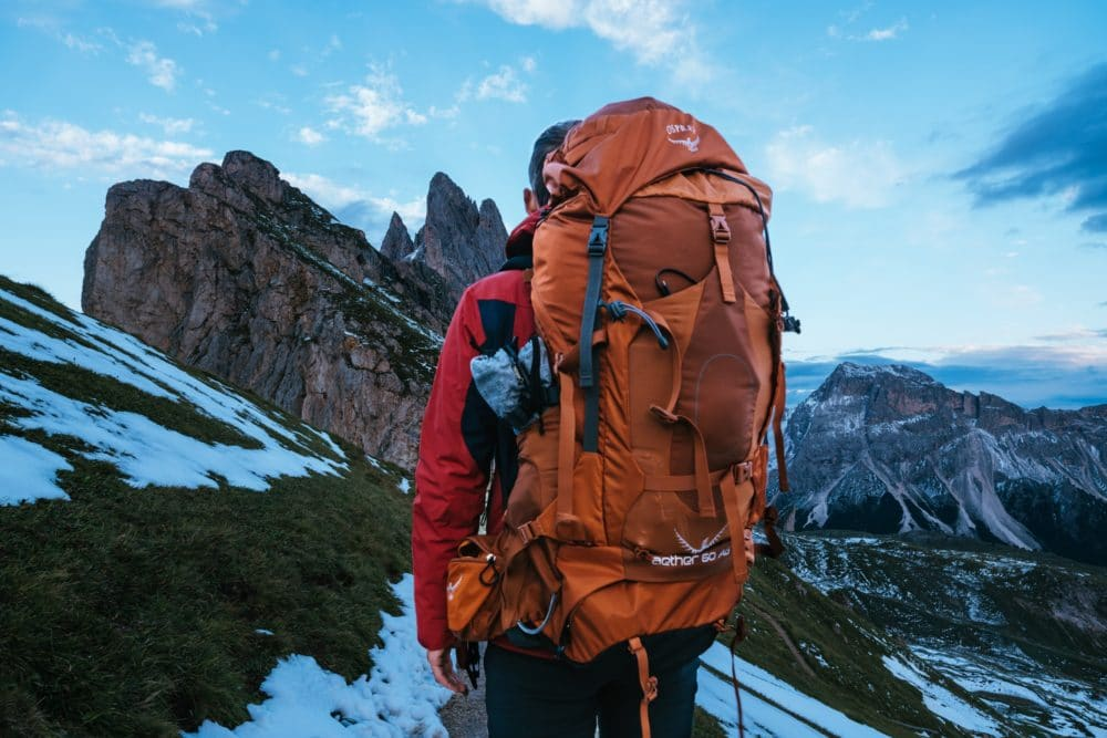 Man carrying a red backpack standing on a mountain in the daytime.