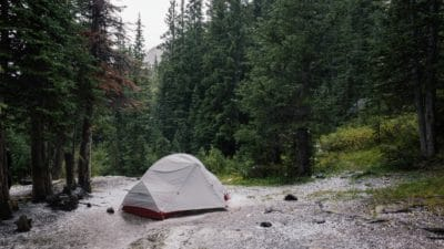 Gray tent beside a lake and surrounded by trees.