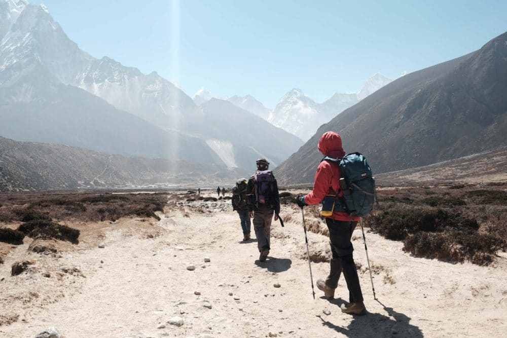People hiking towards mountain ranges.