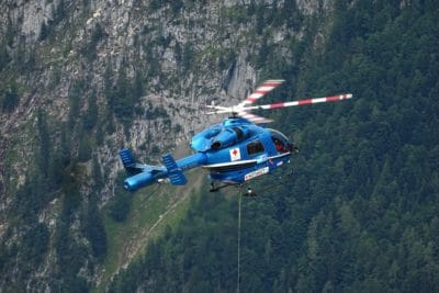Blue and white helicopter in the mountains.