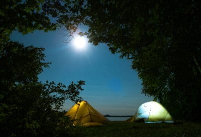 Two tents at night under the moon.
