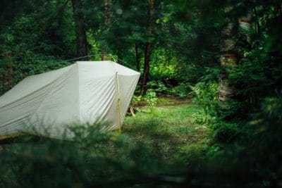 White camping tent in the woods.