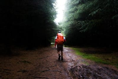 Man with a red waterproofed backpack on a trail in the forest.