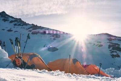Three orange tents in the snow.