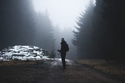 Man standing in the forest in the rain.