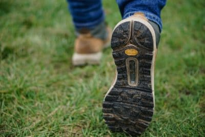 The black rubber sole of a hiking boot in green grass.