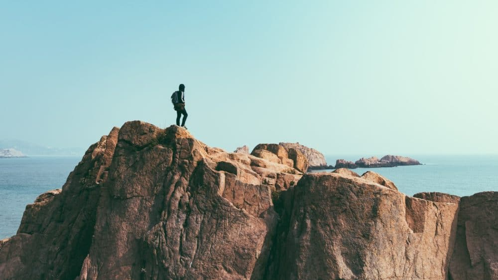 Man stands on top of a mountain.