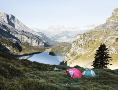 Two tents in a mountain range by the water.