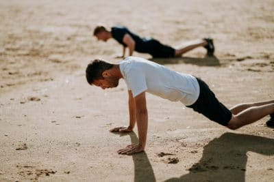 Two men doing pushups in the sand daytime.