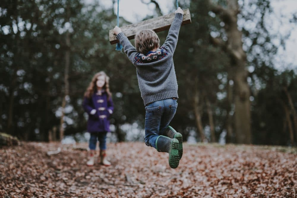 A boy swinging from a tree swing with a girl.