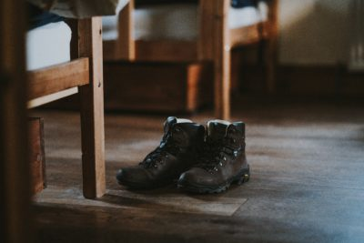 A pair of brown leather hiking boots on a wooden floor in a room.