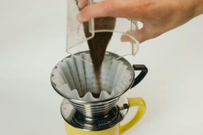 Pouring coffee into a pot with a coffee filter.