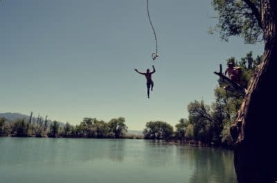 A person swinging from a rope swing over a lake.