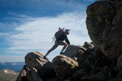 A man climbing on rocks in the daytime.