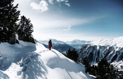 A person hiking in the snow in the mountains.