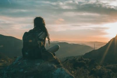 A girl sitting in the mountains during sunset.