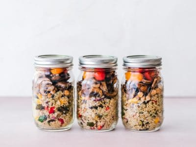 Three glass jars of granola and berries.