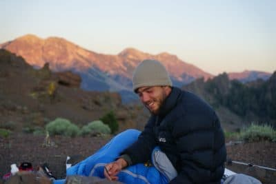 Man sitting and smiling in the mountains.
