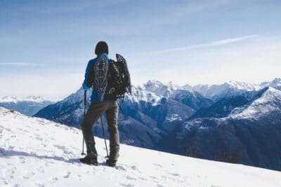 A man with trekking poles in the snowy mountains daytime.