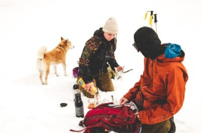 Two people in the snow with a dog.