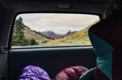 A view through the back of a car of mountains.