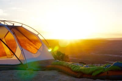 A green sleeping bag next to a tent during sunset.