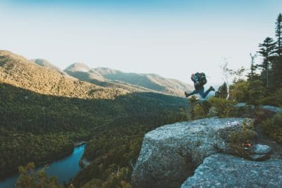 A hiker jumping in the air on a rock cliff.