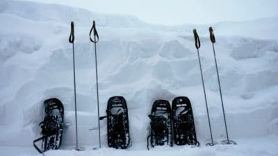Two pairs of snow boots with trekking poles in the snow.